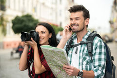 Tourists. Two happy young tourists with backpacks, touristic map and camera. Sightseeing City Royalty Free Stock Image