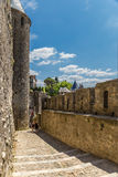Tourists between two rows of defensive walls of the fortress of Carcassonne, France. Fortress of Carcassonne - a medieval architectural complex, located in the Royalty Free Stock Photo