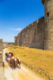 Tourists between two rows of defensive walls of the medieval fortress in Carcassonne, France. Fortress of Carcassonne - a medieval architectural complex, located Stock Image