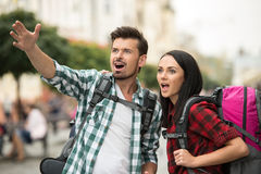 Tourists. Two young tourists with backpacks are sightseeing city Royalty Free Stock Photography