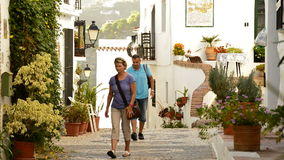Tourists in a typical street of Andalusia. Tourists in a typical andalusian village walking stock video