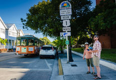 Tourists at U.S. Route 1 - Key West, Florida. Tourists consult map at beginning point of U.S. Route 1. US 1 travels along the east coast of Florida, beginning in Stock Photos