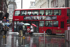 Tourists with umbrella walking against a background of double-decker red bus in Westminster. Raining Royalty Free Stock Image