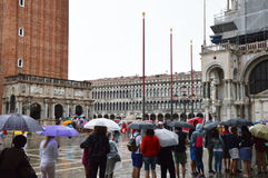 Tourists with umbrellas in St Mark`s square in a raining day, Venice, Italy. Stock Photos