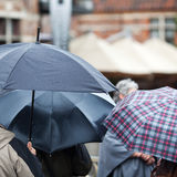 Tourists with umbrellas standing in the rain Stock Photo