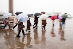 Tourists with umbrellas walking in Venice Stock Images