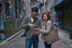 Tourists using map on digital device royalty free stock photography