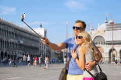Tourists using selfie stick to make photo with smartphone Stock Photo