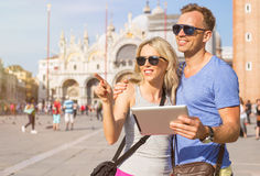 Tourists using tablet computer while traveling Stock Photography