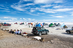 Tourists at the Uyuni Salt Flats. UYUNI, BOLIVIA - JULY 11: Tourists and SUVs seen at the base of Island Incahuasi on the Uyuni Salt Flats in Bolivia on July 11 Royalty Free Stock Image