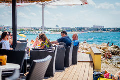 Tourists and various guests sitting at the bar by the sea and enjoy the sun in Zadar Stock Images
