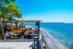 Tourists and various guests sitting at the bar by the sea and enjoy the sun in Zadar Stock Photo