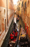 Tourists in Venice. Gondola with asian tourists on small canal in Venice, Italy Royalty Free Stock Photos