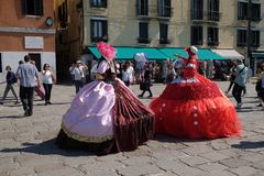 Tourists in Venice on the Grand Canal are welcomed by costumed ladies in Venice. Italy on May 28, 2017 Stock Image