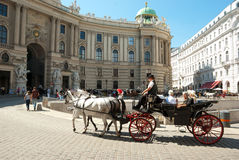 Tourists in Vienna. VIENNA, AUG 22 - Tourists ride through the old town on a cab, visiting the famous landmark - Hofburg Palace at August 22, 2010 in Vienna Royalty Free Stock Images