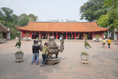 Tourists view ancient bronze incense burner at the Temple of Literature. Hanoi, Vietnam Stock Photos