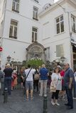 Tourists view Manneken Pis dressed as a shepherd`s suit stock images