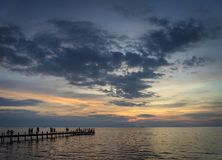Tourists view sunset by pier in kep town cambodia coast. Tourists view sunset by pier in kep town on cambodia coast Stock Photography