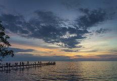Tourists view sunset by pier in kep town cambodia coast. Tourists view sunset by pier in kep town on cambodia coast Stock Photos