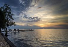 Tourists view sunset by pier in kep town cambodia coast. Tourists view sunset by pier in kep town on cambodia coast Royalty Free Stock Image