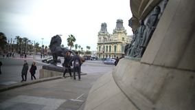Tourists viewing bronze lion sculpture at Columbus Monument base in Barcelona stock video footage