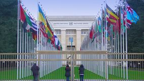 Tourists viewing Palace of Nations in Geneva, alley of UN member countries flags. Stock footage stock video