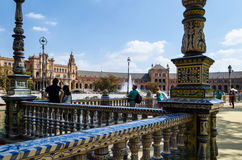 Tourists viewing the Plaza of Spain, Seville, Andalusia, Spain. In the foreground is a ceramic fence in the traditional Spanish style, in the background Royalty Free Stock Image