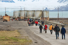 Tourists visit abandoned Russian arctic settlement Pyramiden, Norway. Royalty Free Stock Photo