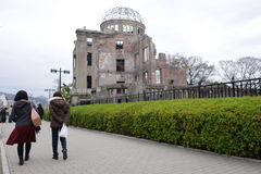 Tourists visit Atomic Bomb Dome in Hiroshima, Japan. HIROSHIMA, JAPAN - DECEMBER 10: Tourists visit Atomic Bomb Dome in Hiroshima, Japan on December 10, 2014 Royalty Free Stock Image