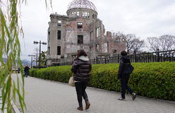 Tourists visit Atomic Bomb Dome in Hiroshima, Japan. HIROSHIMA, JAPAN - DECEMBER 10: Tourists visit Atomic Bomb Dome in Hiroshima, Japan on December 10, 2014 Royalty Free Stock Images