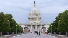 View of East Side of Capitol Building. 9078 Tourists visit the Capitol Building on Capitol Hill on an overcast summer day stock footage