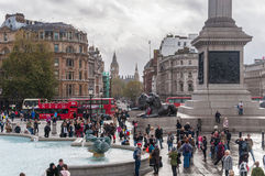 Tourists visit Trafalgar Square in London on a cloudy day Stock Image