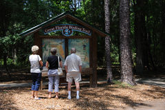 Tourists visiting American state park USA. Visitors at Paynes Prairie Preserve State Park in Florida USA standing at the Great Florida Birding Trail info point royalty free stock images