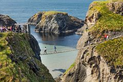 Tourists visiting Carrick-a-Rede Rope Bridge in County Antrim of Northern Ireland stock photos