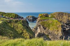Tourists visiting Carrick-a-Rede Rope Bridge in County Antrim of Northern Ireland. Thousands of tourists visiting Carrick-a-Rede Rope Bridge in County Antrim of stock photo