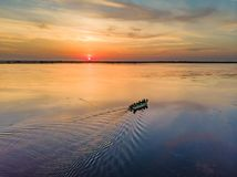 Tourists visiting Danube Delta at sunset in a motor boat. Sunset. In Danube Delta Delta Dunarii, Europe, Romania stock photography