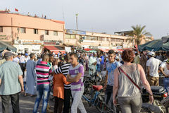 Tourists visiting Djemaa el Fna - market place in Marrakesh's medina quarter on 24 August 2014 in Marrakesh, Morocco. Stock Photo