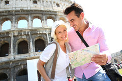 Tourists visiting Rome with help of map. Tourists reading map in front of the Coliseum, Rome Royalty Free Stock Photography