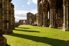Tourists visiting the ruins of Whitby Abbey Stock Photo
