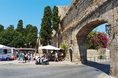 Tourists are visiting souvenir shops near the old arch of Rhodes town fortress. RHODES, GREECE - AUGUST 2017: Tourists are visiting souvenir shops near the old Royalty Free Stock Images