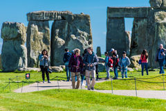 Tourists visiting Stonehenge. A group of EU tourist visiting the ancient ruins of Stonehenge. Stonehenge, historical monument in England. UK, during a warm stock photos