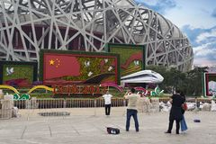 Tourists visiting and taking photos in front of the Beijing National Stadium also called the Bird`s Nest in Bejing, China stock photos
