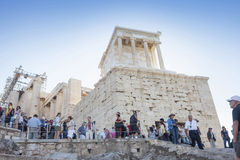 Tourists visiting Temple of Athena Nike. ATHENS, GREECE - OCTOBER 6: Tourists sightseeing the ruins of the Temple of Athena Nike in the Acropolis of Athens on Stock Photos