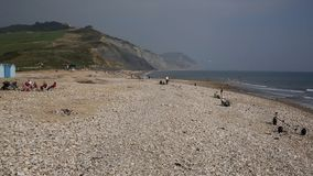 Tourists and visitors Charmouth beach in Dorset overlooking Lyme Bay stock footage