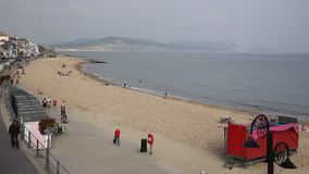 Tourists and visitors Lyme Regis beach Dorset England UK in Lyme Bay stock footage
