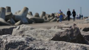 Tourists and visitors walking the rocks of jetty and breakwater to entrance of Klasipeda harbor. stock video