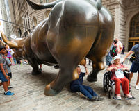 Tourists visits the Wall Street Charging Bull statue Stock Image