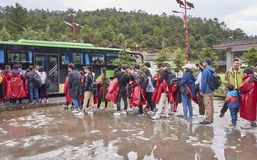 Tourists wait in line for a bus in Blue Moon Valley scenic area on a rainy day. Stock Image