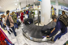 Tourists wait for their baggage Stock Image