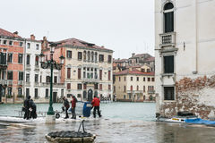 Tourists wait water bus in Venice city in rain Royalty Free Stock Images